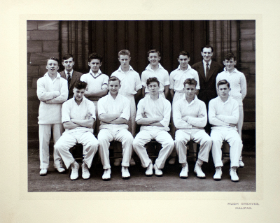 Formal photograph showing eleven players of a 1950s Cricket Team in two rows of five seated and six standing with the scorer and Mr A.E. Carter in the back row