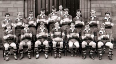 Formal photograph showing nine players standing behind seven seated players with Mr Birchall standing at the very back