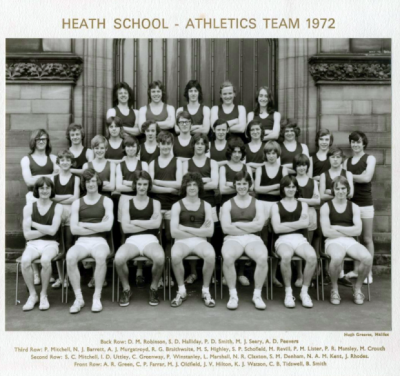 Formal photograph showing team members in three rows standing on the front steps of the school behind seven seated team members