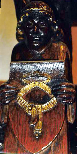 Angel holding a wooden shield on which is engraved the belt of truth