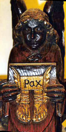 Angel holding a wooden shield on which are engraved the shoes of peace below the word Pax