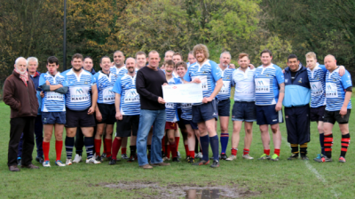 Jon Hamer presents the cheque to Stuart Hill with the Magpies team looking on