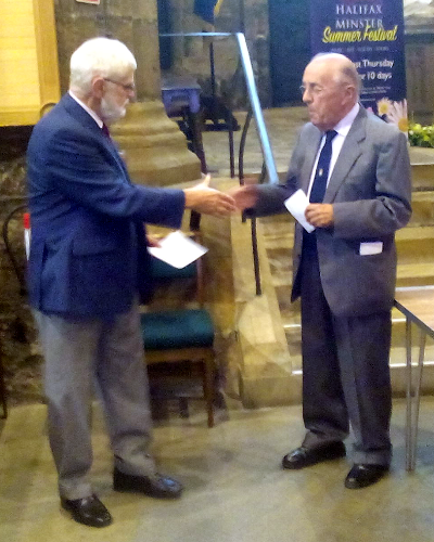 Grayham P. Smith on the left presenting the cheque to John Hoggard in Halifax Minster