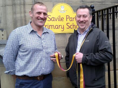 Jon Hamer and Jim Farrell holding a ribbon in the schools' colours, claret and gold, in front of Heath school